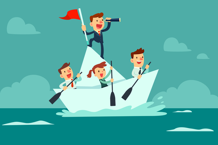 business team sailing on a paper boat