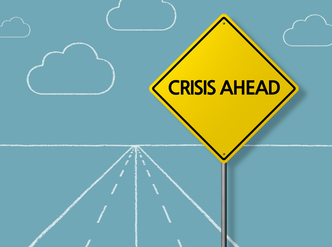 crisis ahead sign on chalkboard road