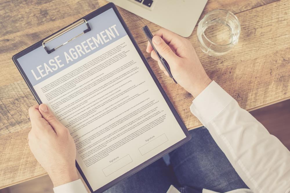 person holding lease agreement and pen