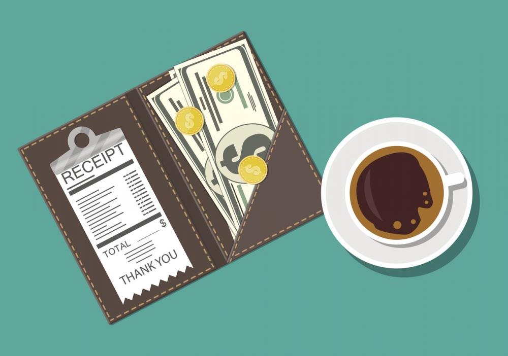receipt book with cash and coins next to a cup of coffee