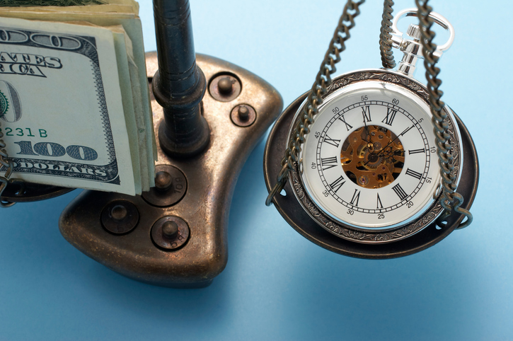 stack of money and pocket watch balanced on a scale