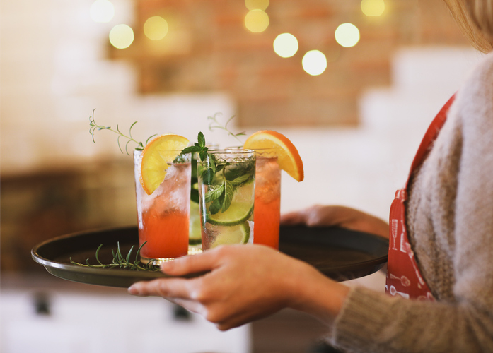 waitress delivering red and green cocktails on a tray
