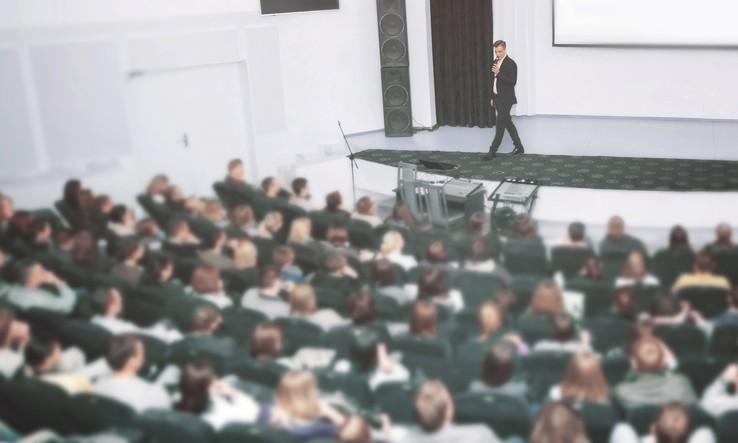 speaker on stage talks to audience