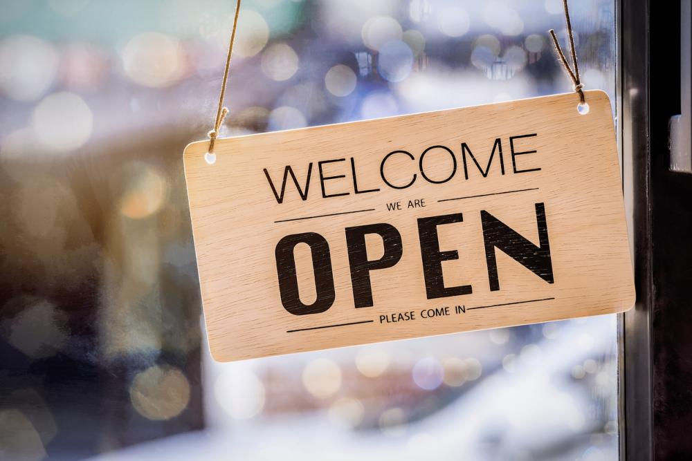 "wooden ""welcome we are open please come in"" sign"