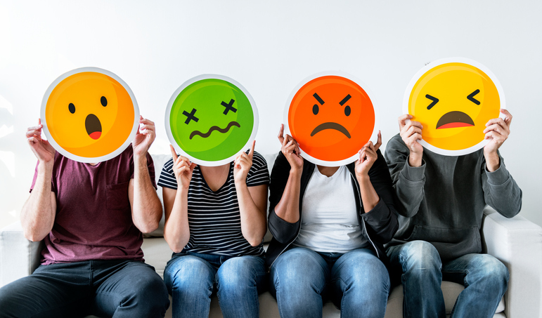 four people holding emoticons