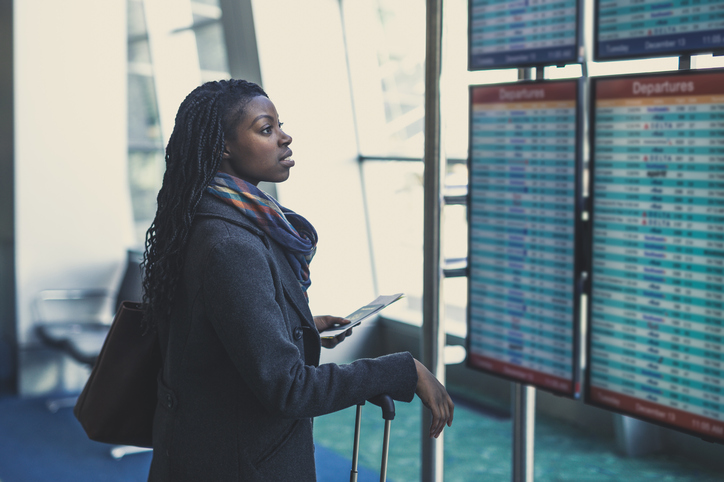 woman reading departures board at airport