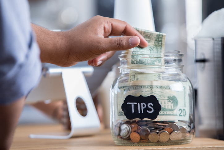 person placing money into tip jar