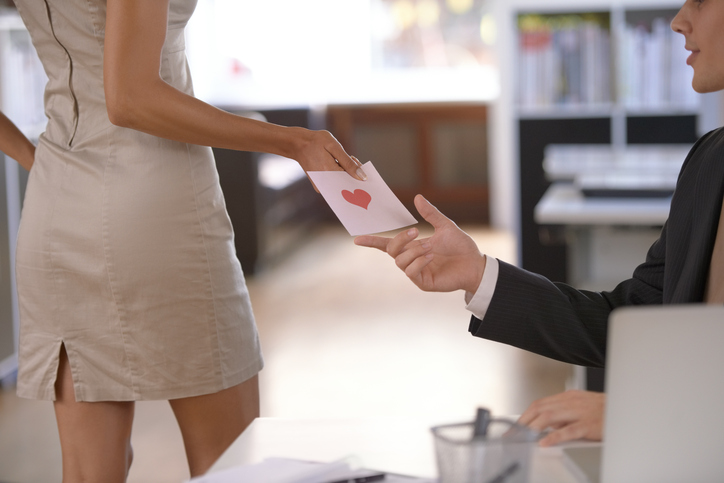 Female employee hands love letter to male employee
