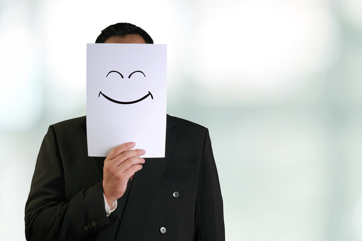 businessperson with paper smiling mask