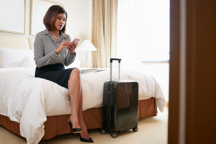 businesswoman texting in hotel room