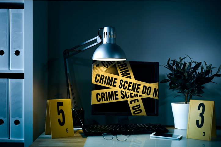 computer covered in crime scene tape