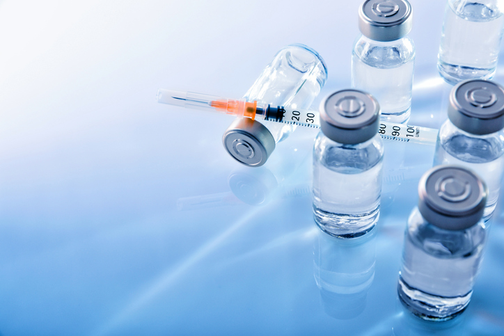 vials and syringe on a blue table top