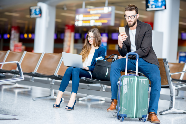 business couple at the airport on electronic devices