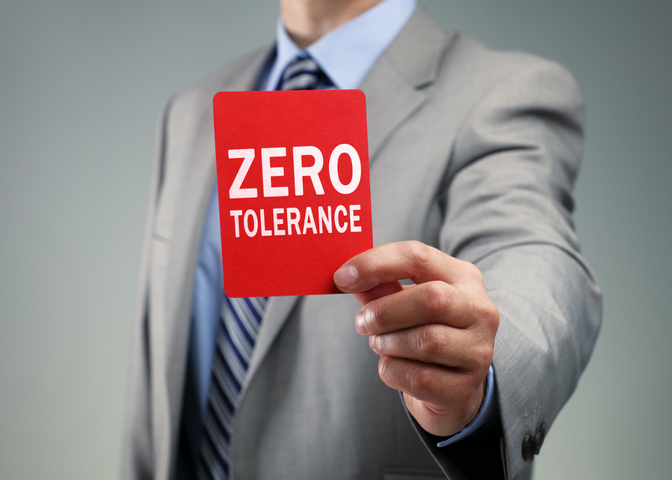 businessman holding red zero tolerance sign