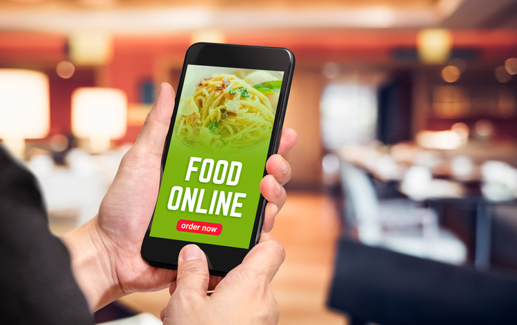 Close up hand holding mobile phone with order food online word on screen