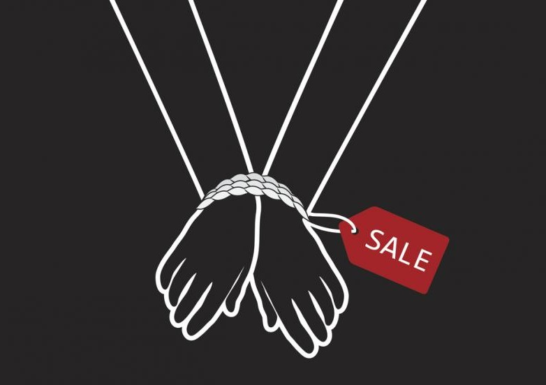 human trafficking concept: hands bound by rope with a sale tag attached