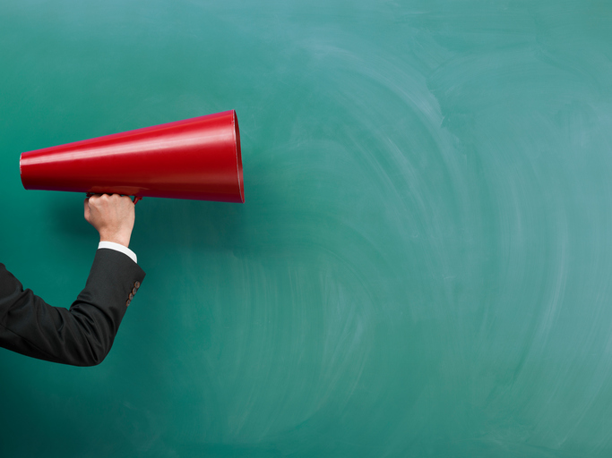 red megaphone being held by a businessman's arm in front a blackboard
