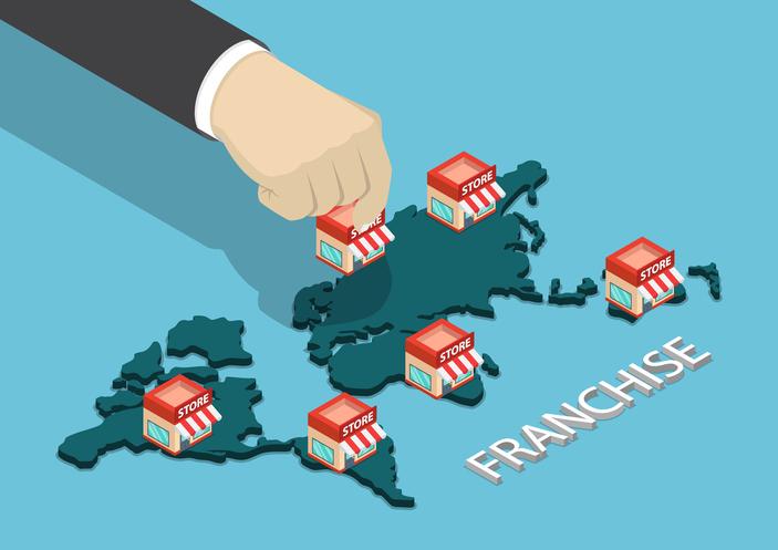 businessman hand put franchise store on world map