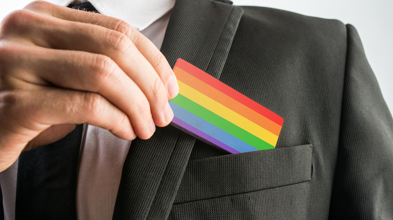 businessman pulls out card designed with lgbt pride flag