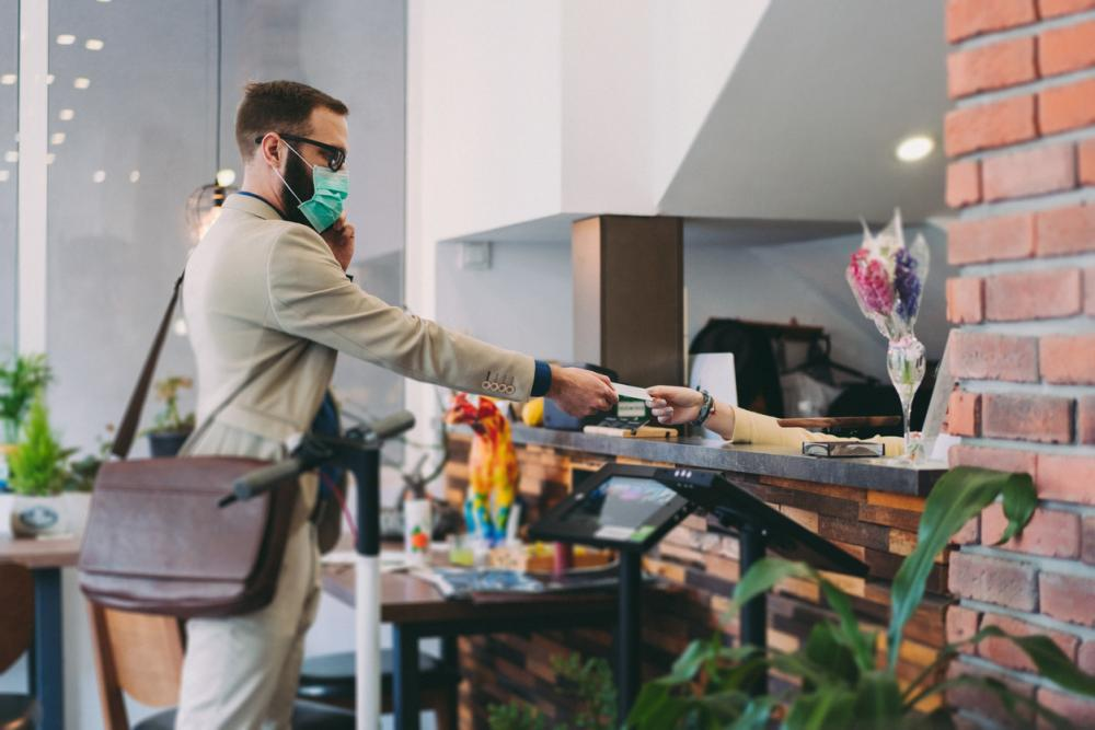 a business traveler wearing a face mask checks into a hotel