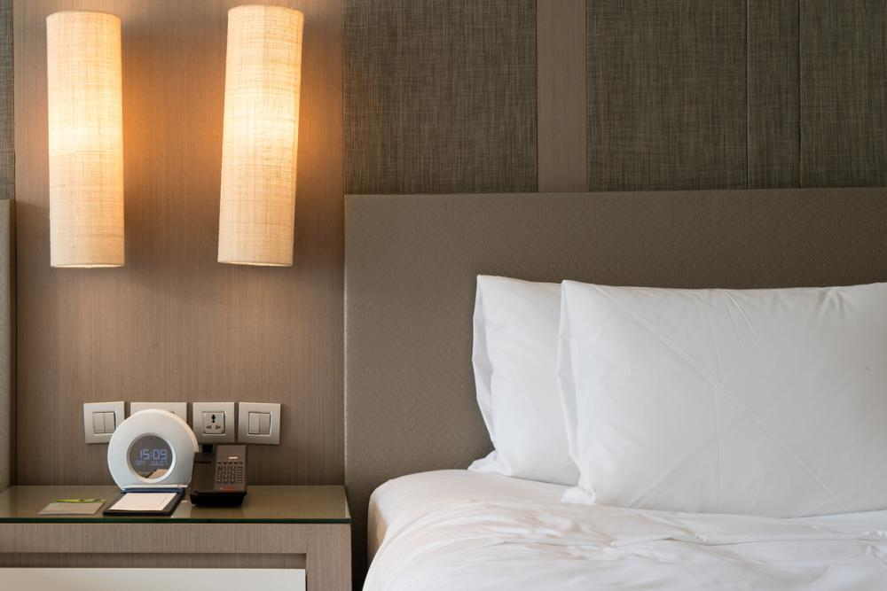 Close up fragment of bedroom with reading lamp and digital alarm clock in hotel.