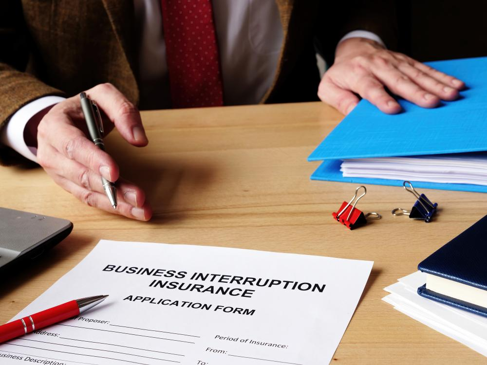 Agent offers business interruption insurance application papers.
