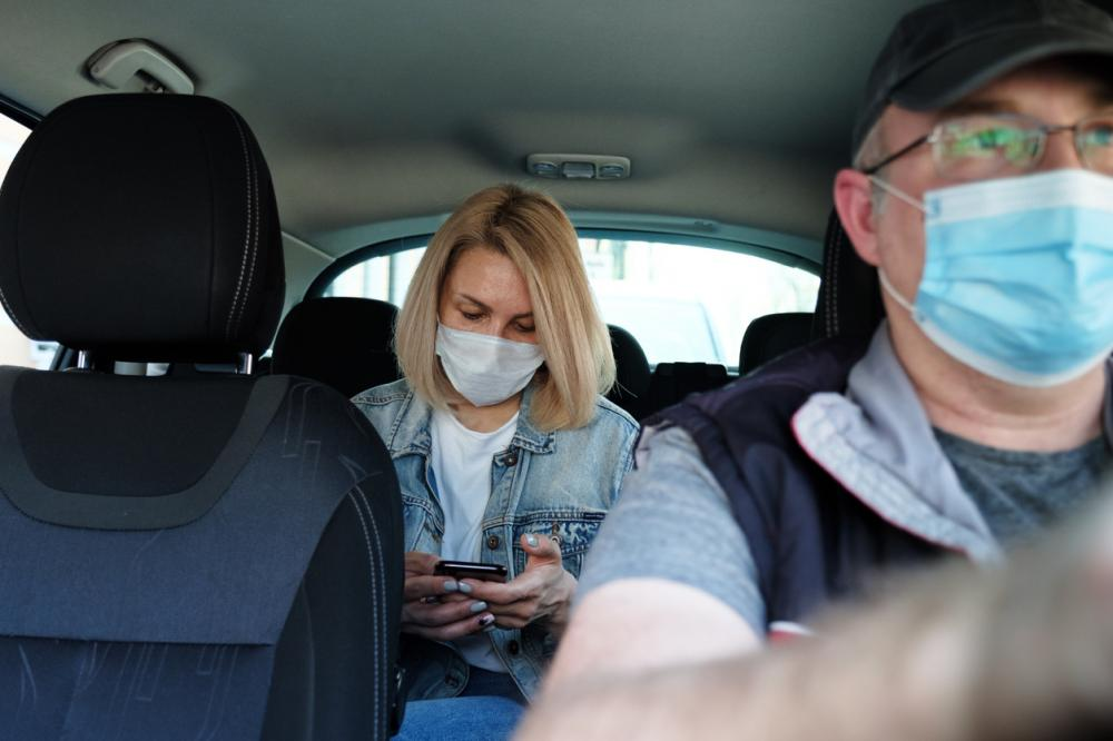 Caucasian woman in rideshare wearing face mask for protection from pollution and viruses such as Coronavirus.