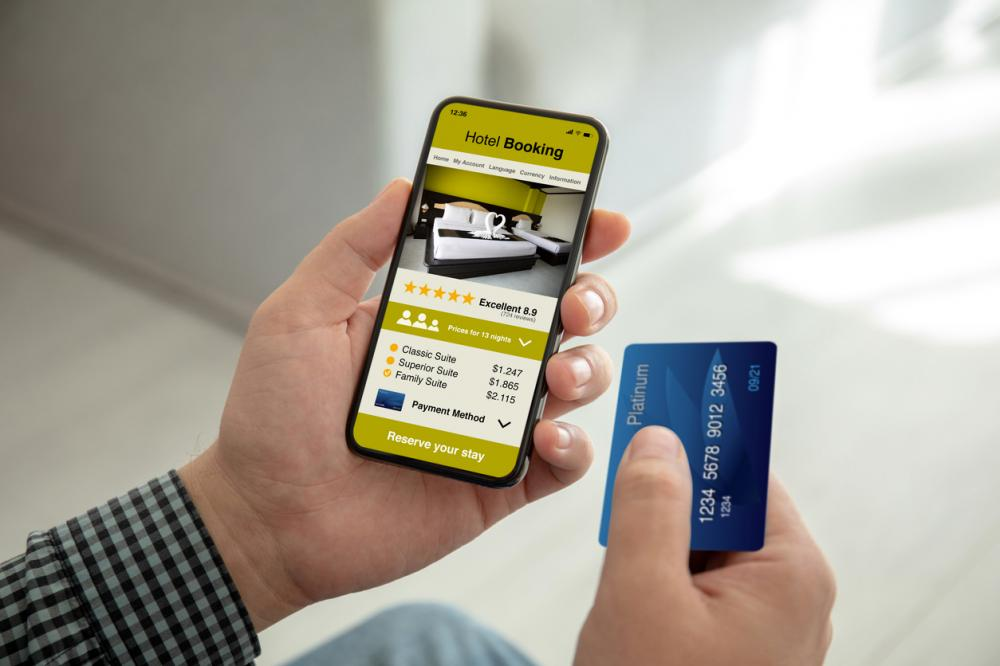 Male hands holding phone with app hotel booking on screen