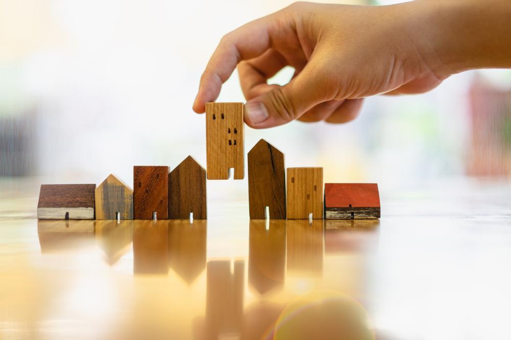 Hand choosing mini wood building model from row