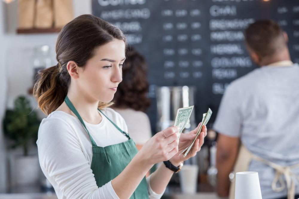 unhappy barista counts money