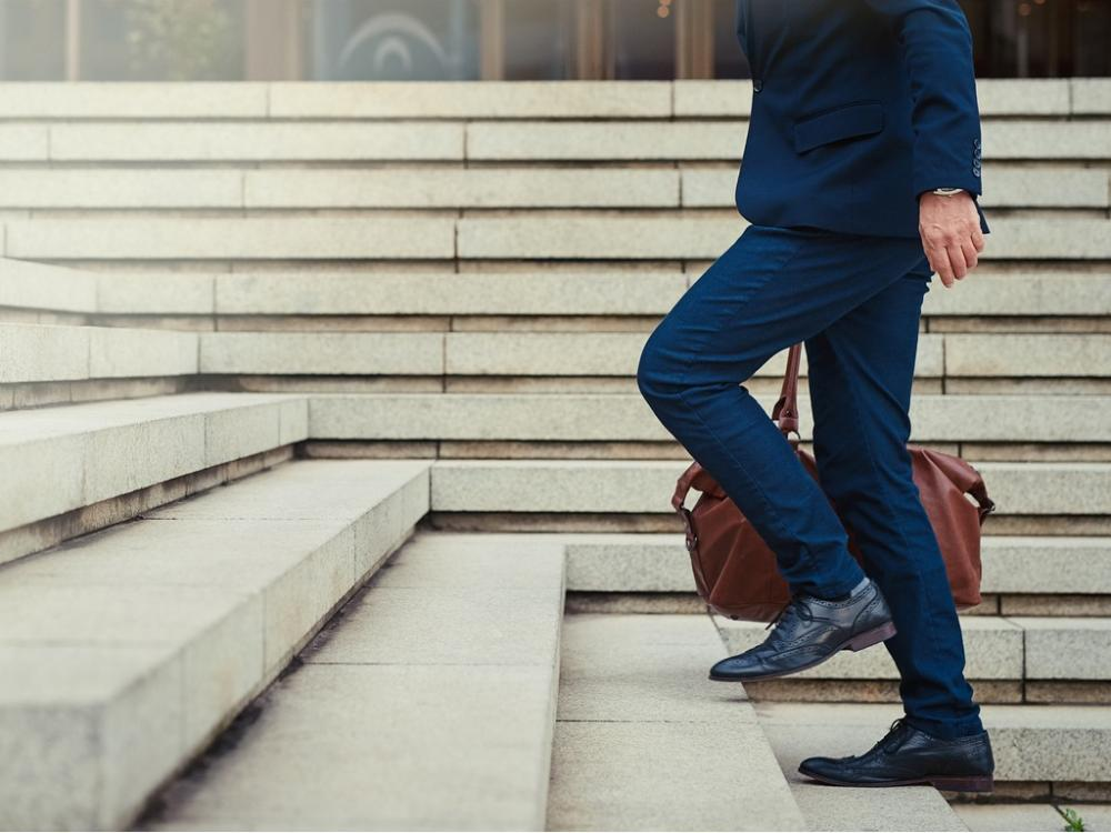 businessman walking up stairs with travel bag