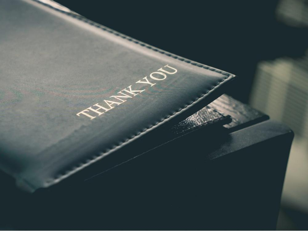 "Restaurant bill folder with writing ""thank you"""