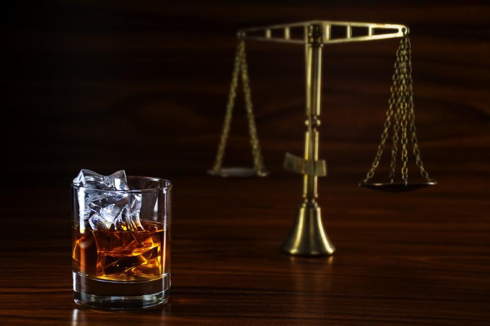 Scales of justice behind a glass of whiskey