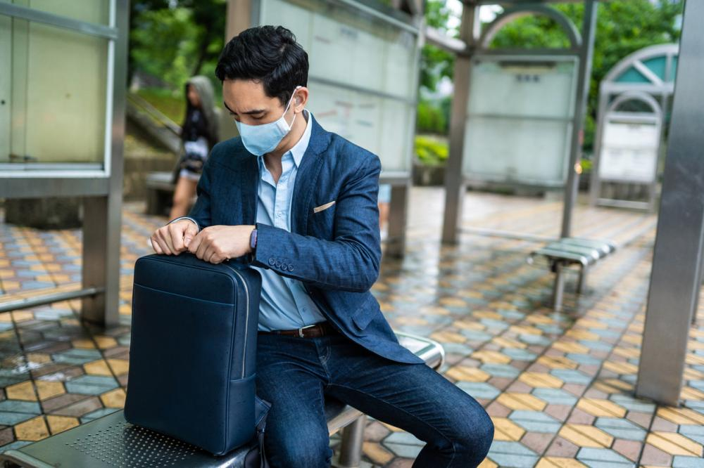Businessman with mask for air pollution sitting on bus station