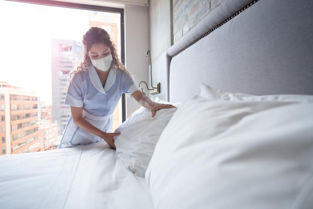 housekeeper with face masks cleans a bed
