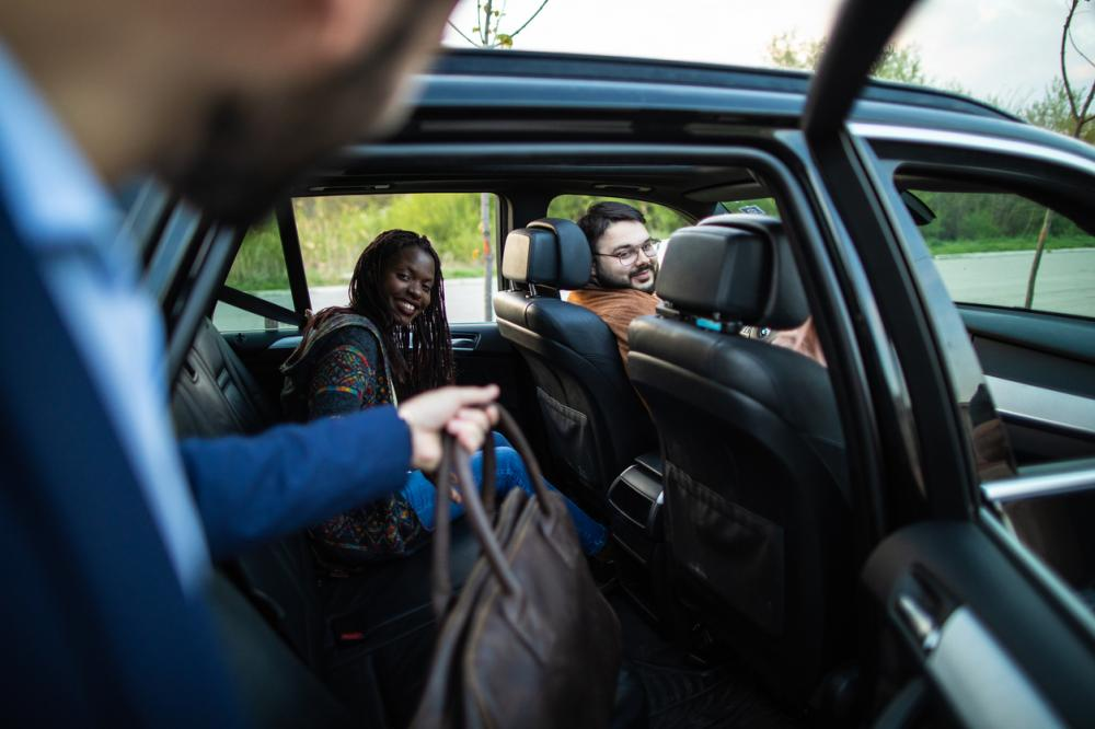 businessman entering ride-sharing car