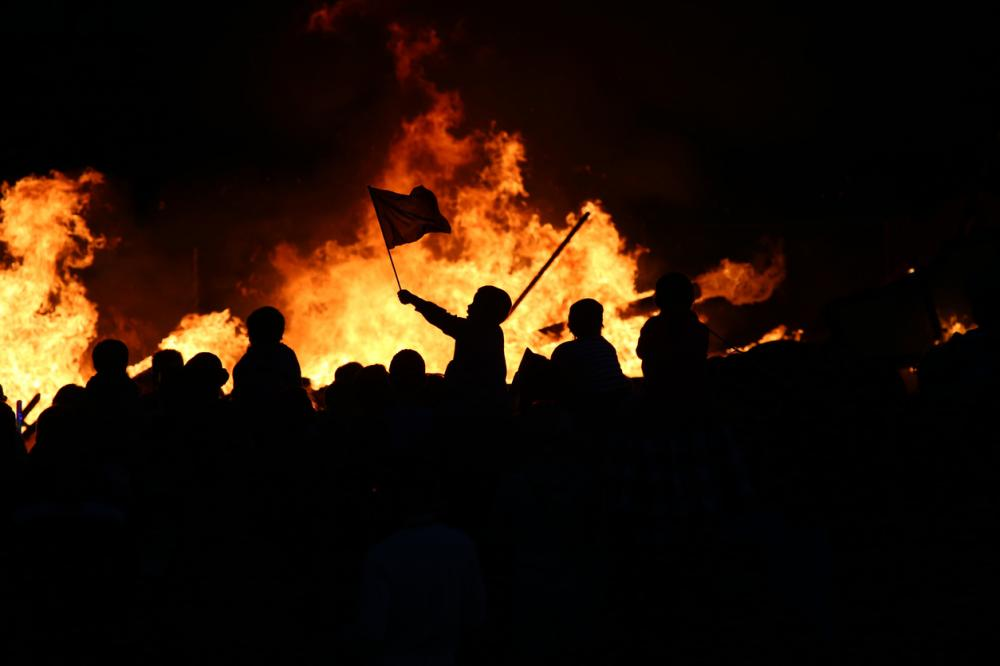civil unrest image, silhouttes in front of a fire