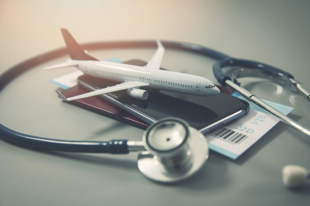 travel health concept: miniature plane, passport, flight ticket, and stethoscope piled together
