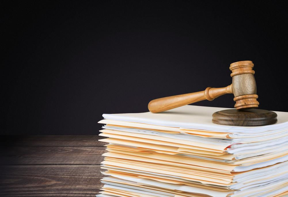 wooden gavel on stack of files