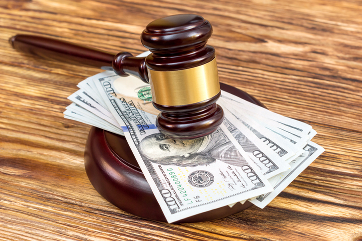 gavel and stand with US dollar bills on table