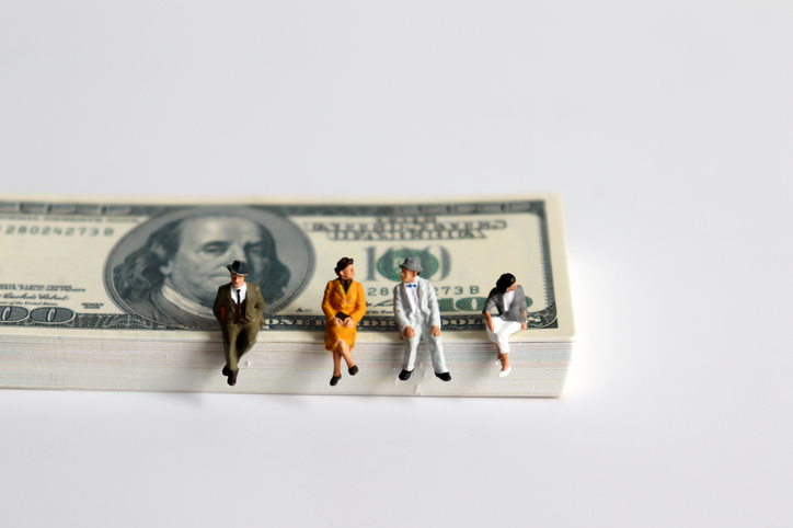 miniature human figurines sitting on stack of bills