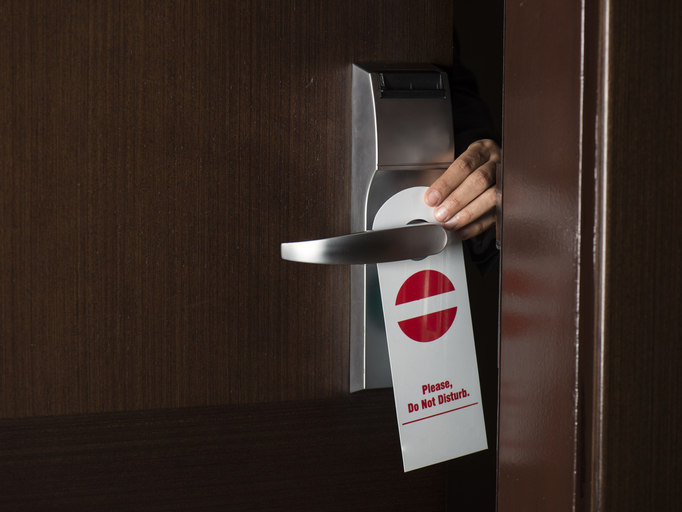 Do Not Disturb sign being placed on hotel door handle
