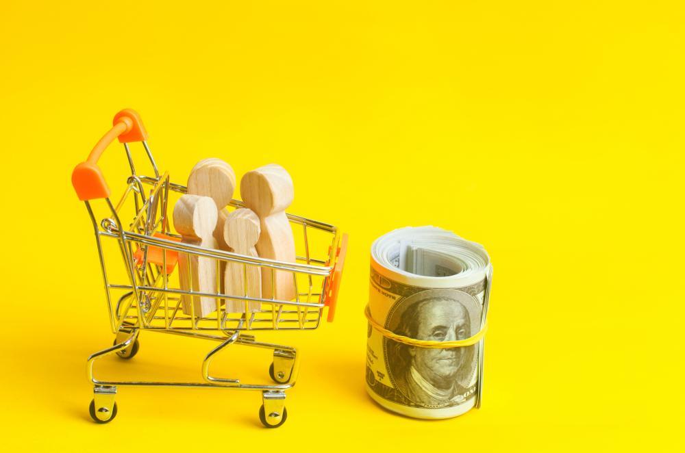 wooden figures in cart next to roll of bills