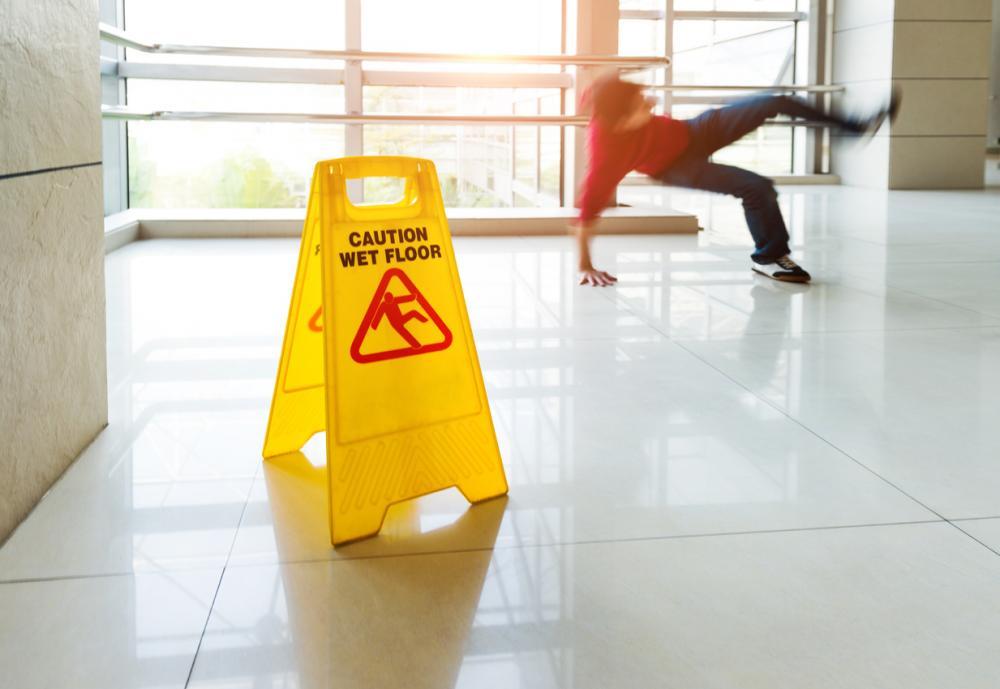 man slipping behind wet floor sign