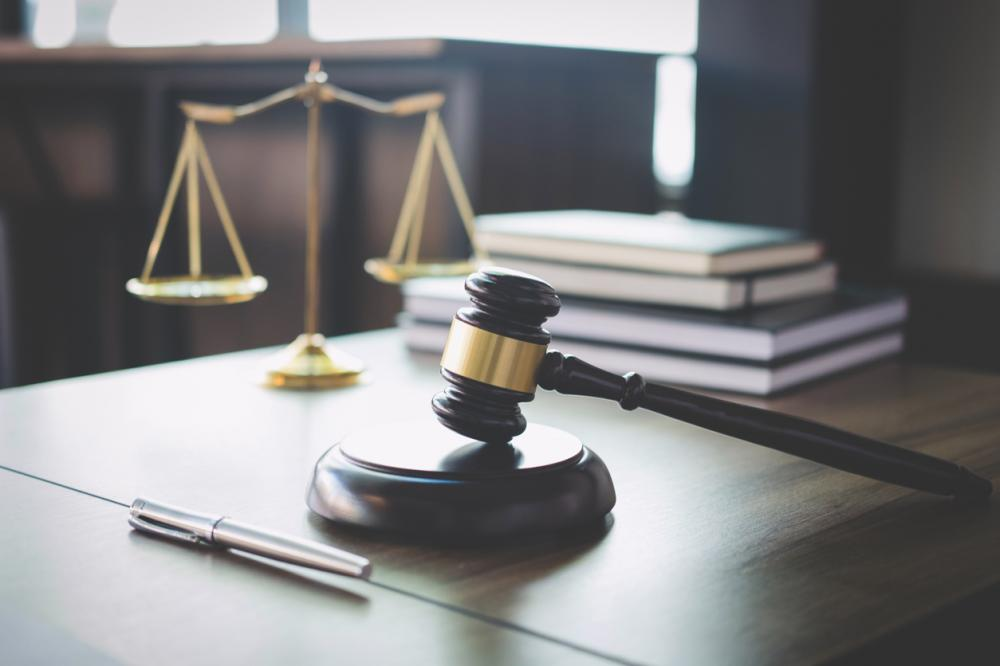 scales of justice and gavel on wooden desk