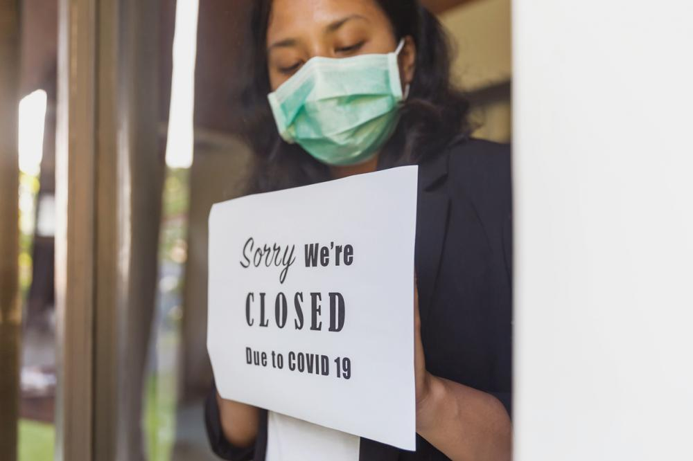 Employee places sign reading 'Sorry we're closed due to COVID-19' on door