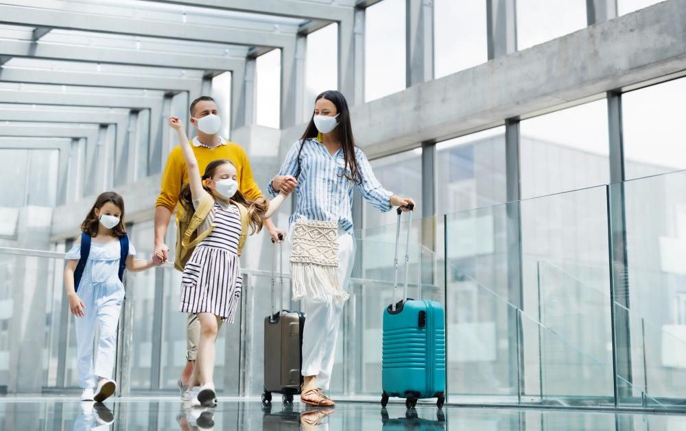 family in masks travelling through airport with luggage