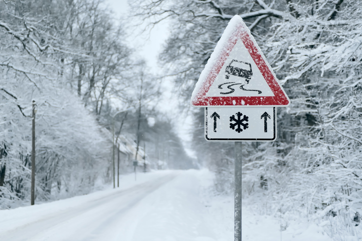 slippery road sign in front of snow-covered road