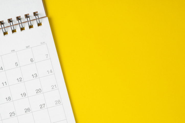 white calendar against solid yellow background
