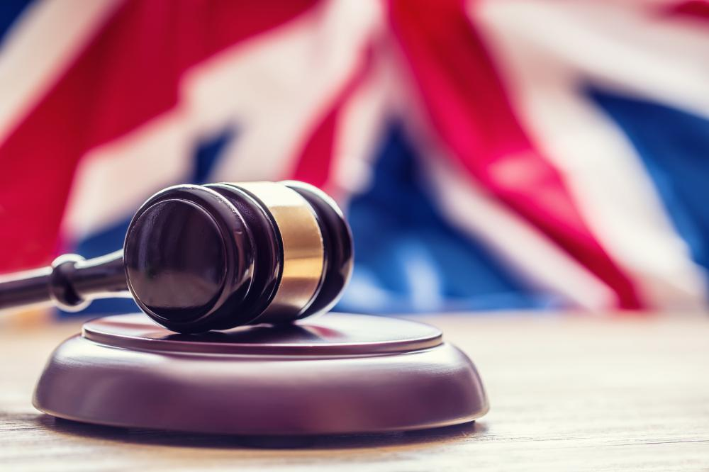 Judges wooden gavel with UK flag in the background